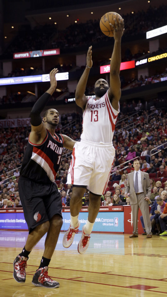 Photo - Houston Rockets' James Harden (13) goes up for a shot a Portland Trail Blazers' LaMarcus Aldridge (12) defends during the third quarter of an NBA basketball game Sunday, March 9, 2014, in Houston. The Rockets won in overtime 118-113. (AP Photo/David J. Phillip)