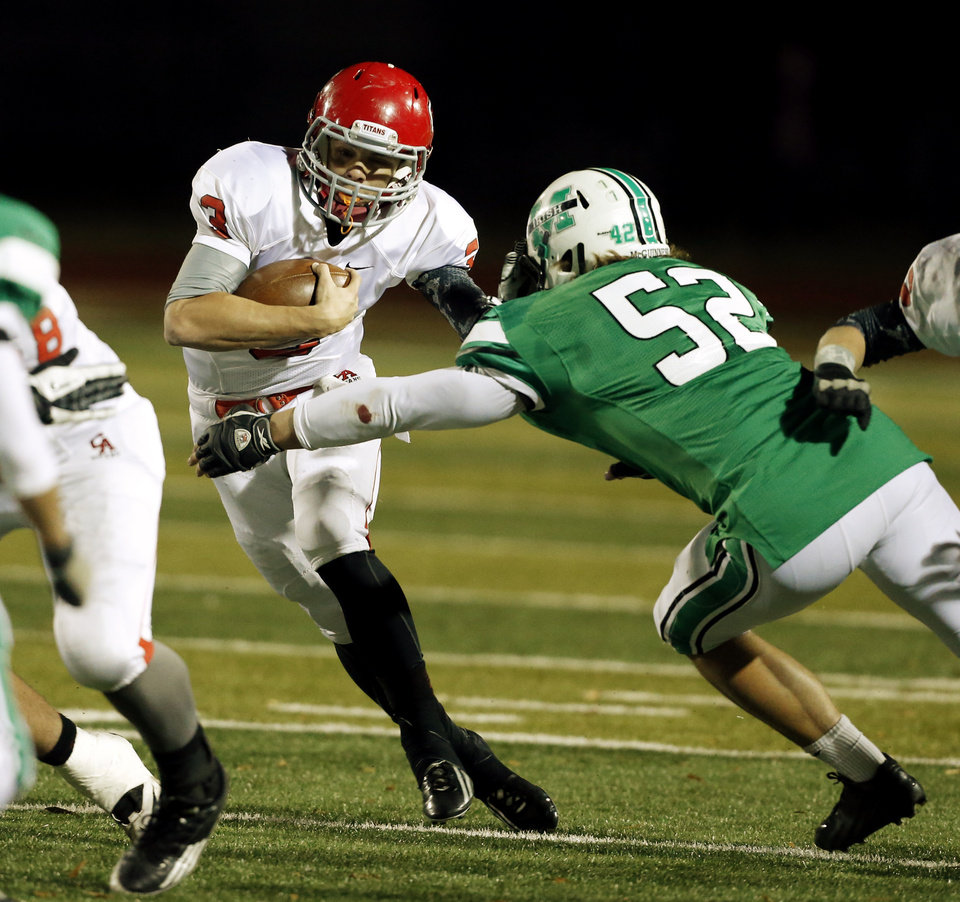 Photo - Titan quarterback Steven Thompson keeps the ball and tries to escape the grasp of Nick Jeffreys (52) as the Bishop McGuinness Irish play the Carl Albert Titans in a Class 5A semi-final playoff game at Harve Collins Field on Friday, Nov. 23, 2012  in Norman, Okla. Photo by Steve Sisney, The Oklahoman