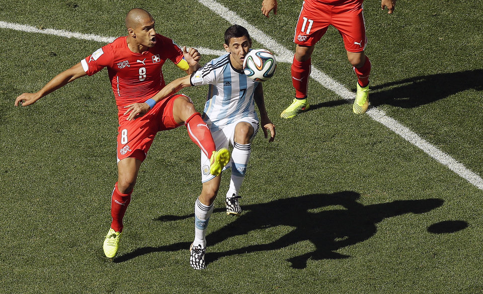 Photo - Switzerland's Goekhan Inler, left, and Argentina's Angel di Maria challenge for the ball during the World Cup round of 16 soccer match between Argentina and Switzerland at the Itaquerao Stadium in Sao Paulo, Brazil, Tuesday, July 1, 2014. (AP Photo/Thanassis Stavrakis)