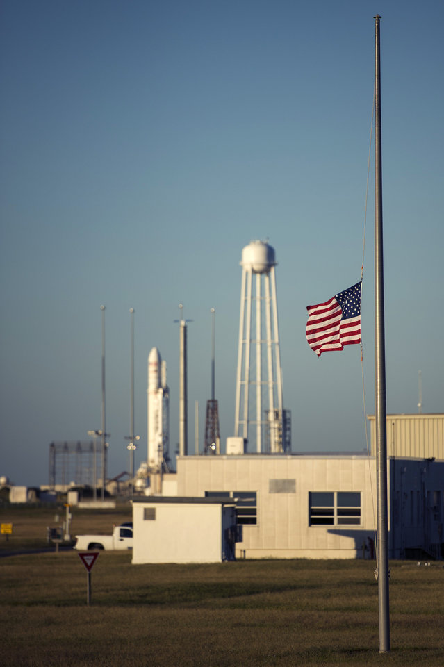 Photo - This photo provided by NASA show a United States flag is flown at half-staff just outside the Mid-Atlantic Regional Spaceport (MARS) Pad-0A with the Orbital Sciences Corporation Antares rocket, Tuesday, Sept. 17, 2013 at Wallops Island, Va.   President Barack Obama  directed that flags be lowered to half-staff to pay tribute to the victims of  the Washington Navy Yard shootings.  NASA's commercial space partner, Orbital Sciences Corporation, is targeting a Sept. 18 launch of the Cygnus cargo spacecraft, demonstration cargo resupply mission, to the International Space Station.   (AP PHoto/NASA, Bill Ingalls)