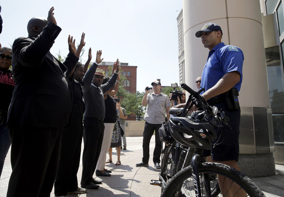 Photo - A member of the St. Louis Police Department blocks the doors of Thomas F. Eagleton federal courthouse as protesters demonstrate outside, Tuesday, Aug. 26, 2014, in St. Louis. About 100 protesters marched as they continue to press for broader reforms to local and federal law enforcement following the shooting death of Michael Brown by police. (AP Photo/Jeff Roberson)