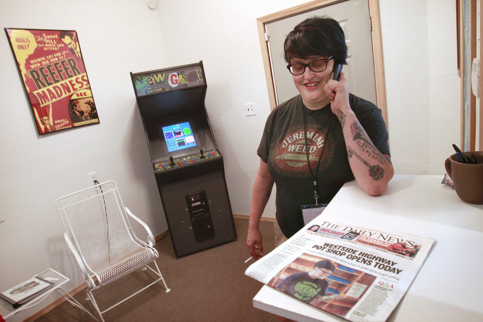 Photo - Co-owner Hollie Hillman talks on the phone with a grower as she waits inside her medical marijuana clinic for her first delivery of state-approved recreational marijuana so that she can begin sales across the parking lot at The Freedom Market in Kelso, Wash., on Tuesday, July 4, 2014. (AP Photo/The Olympian, Tony Overman)