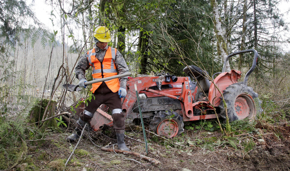 Photo - A searcher makes his way past a tractor that landed at the edge of the debris field after being tossed about in a deadly mudslide, Wednesday, April 2, 2014, in Oso, Wash. Officials have so far confirmed the deaths of 29 people, although only 22 have been officially identified in information released Wednesday morning by the Snohomish County medical examiner's office. (AP Photo/Elaine Thompson)