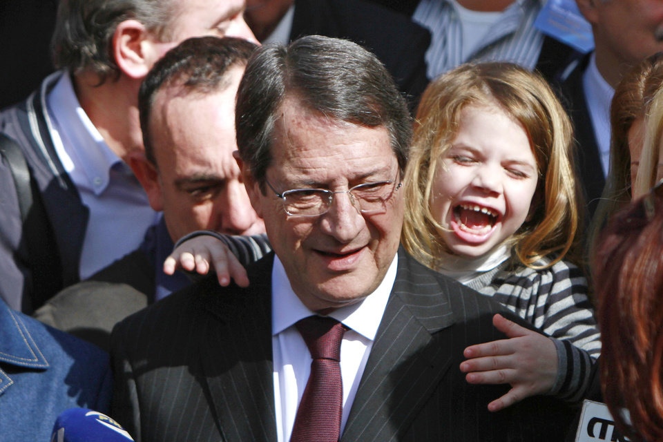 Photo - Right-wing opposition leader and presidential candidate Nicos Anastasiades with his granddaughter Nikoletta leaves after voting in the presidential election in southern port city of Limassol, Cyprus, Sunday, Feb. 24, 2013. Anastasiades garnered 45.46 per cent of the vote in the first round of voting, some 18 points over communist-backed Stavros Malas. (AP Photo/Petros Karadjias)