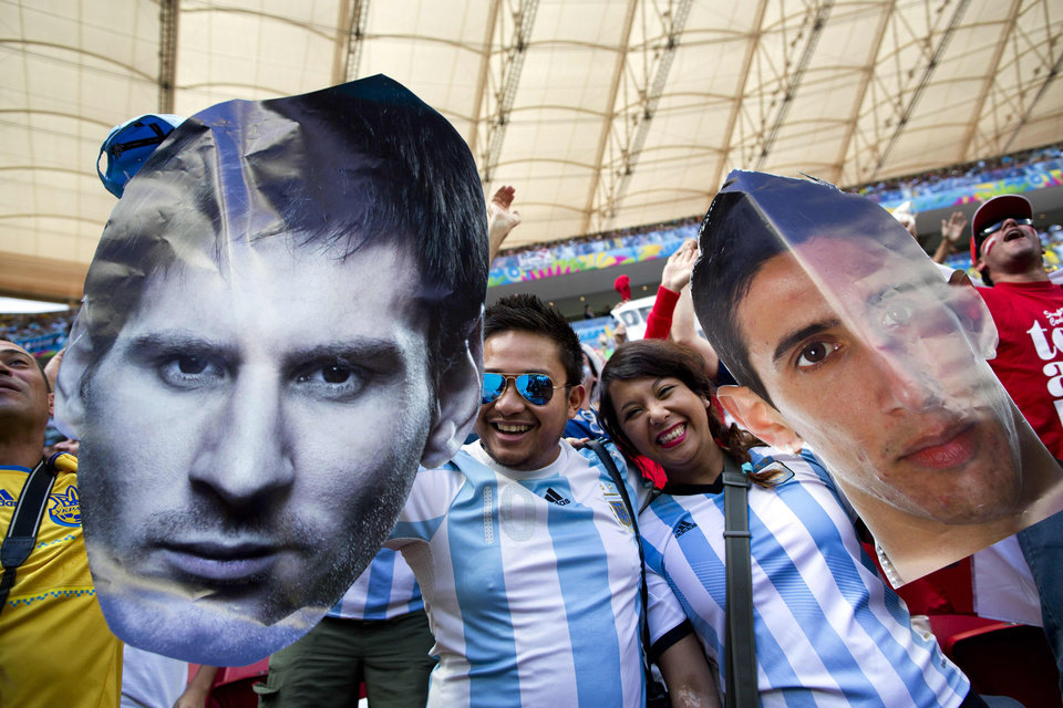 Photo - Fans of Argentina's national soccer team hold face cutouts of Lionel Messi, left, and Angel Di Maria, during the World Cup quarterfinal match between Argentina and Belgium at the Estadio Nacional  in Brasilia, Brazil, Saturday, July 5, 2014. (AP Photo/Rodrigo Abd)
