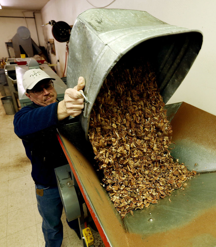 Brett Mason with Mason's Pecans & Peanuts loads cracked and shaken pecans into a machine to blow off shells. PHOTO BY STEVE SISNEY, THE OKLAHOMAN <strong>STEVE SISNEY</strong>