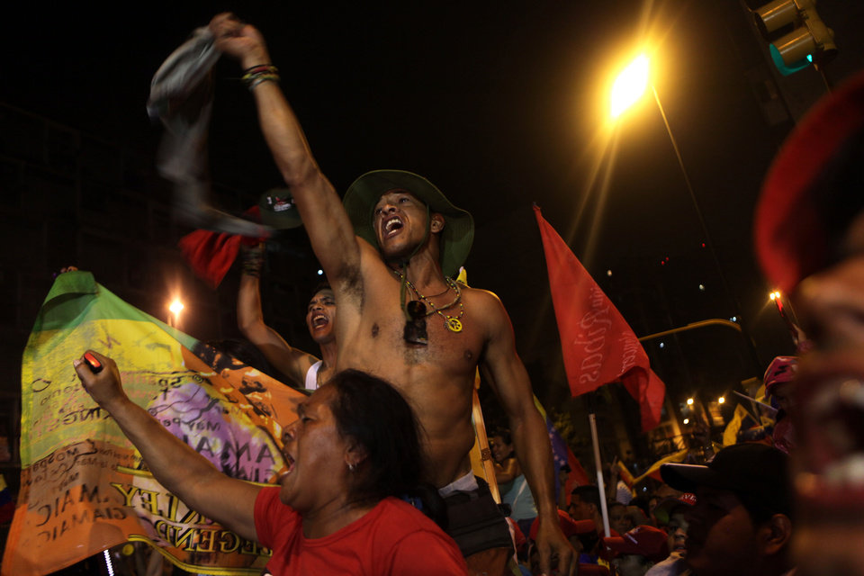 Photo -   Supporters of Venezuela's President Hugo Chavez celebrate at the Miraflores presidential palace late Sunday Oct. 7, 2012. Chavez won re-election and a new endorsement of his socialist project Sunday, surviving his closest race yet after a bitter campaign against opposition candidate Henrique Capriles.(AP Photo/Rodrigo Abd)