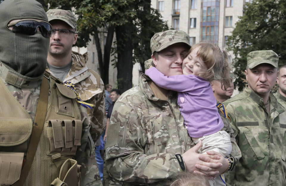 Photo - A father, a volunteer, holds his little daughter as relatives and friends say good-buy to volunteers before they were sent to the eastern part of Ukraine to join the ranks of special battalion unit fighting against pro-Russian separatists, in Kiev, Ukraine, Tuesday, Aug. 26, 2014. It was the second straight day that attacks were reported in the vicinity of Novoazovsk, which is in eastern Ukraine's separatist Donetsk region but previously had seen little fighting between Ukrainian forces and pro-Russian rebels. (AP Photo/Efrem Lukatsky)