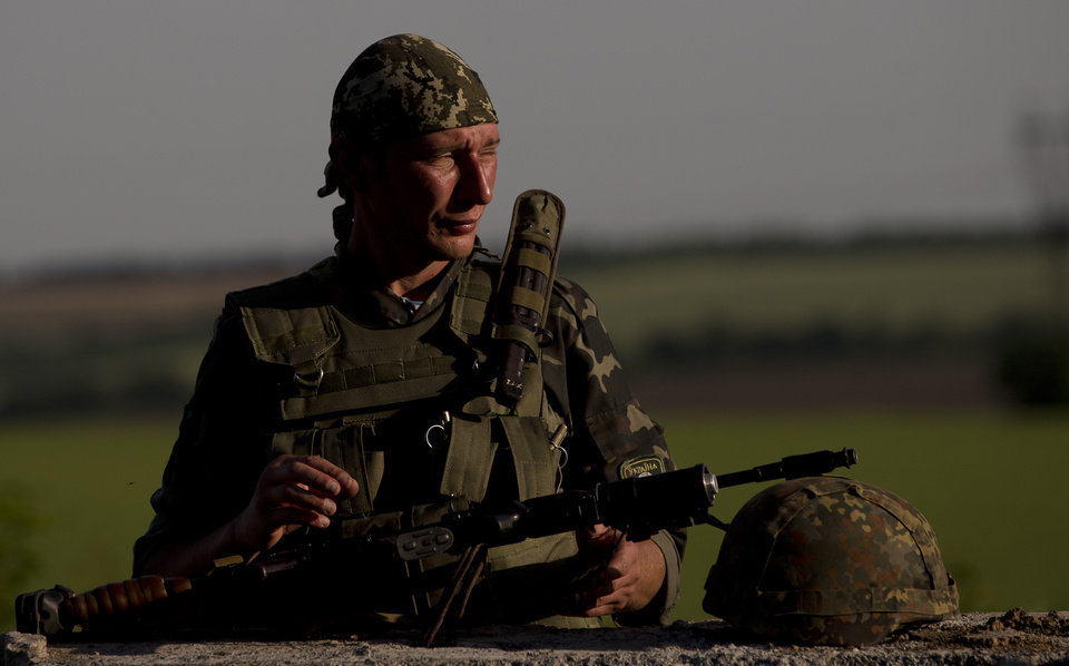 Photo - An Ukrainian soldier observes the road at a checkpoint outside the town of Amvrosiivka, eastern Ukraine, close to the Russian border, Thursday, June 5, 2014. The Ukrainian military was on alert on its eastern border with Russia on Thursday amid reports that separatist forces launched attacks on a border crossing near the village of Marinyvka.(AP Photo/Vadim Ghirda)