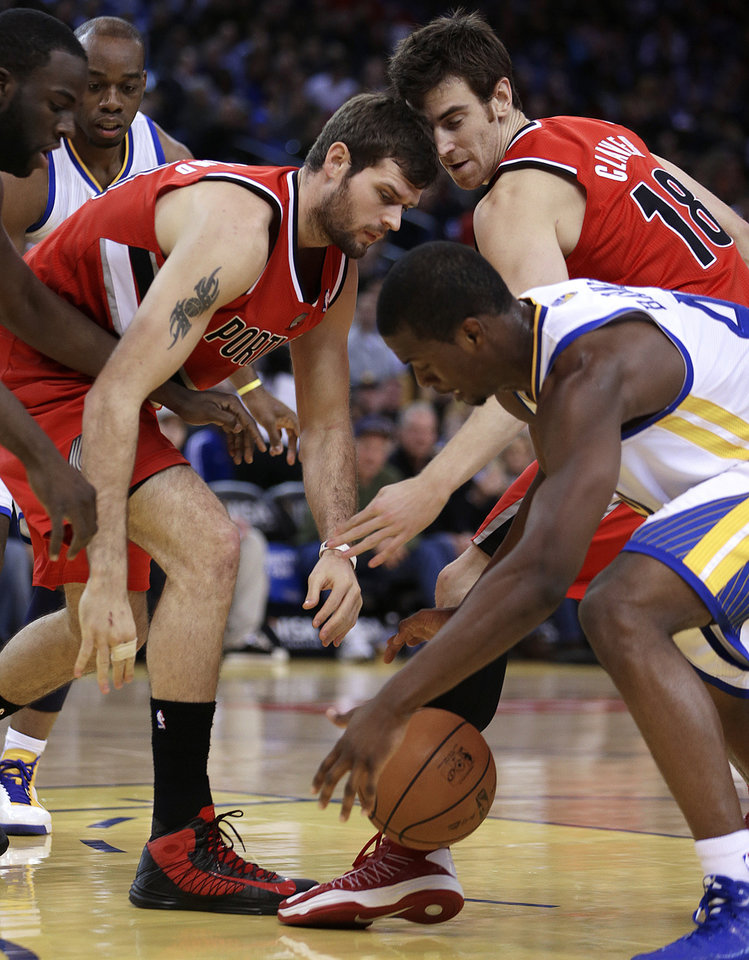 Portland Trail Blazers' Joel Freeland, left, Victor Claver (18), and Golden State Warriors'  Harrison Barnes chase a loose ball during the first half of an NBA basketball game Friday, Jan. 11, 2013, in Oakland, Calif. (AP Photo/Ben Margot)