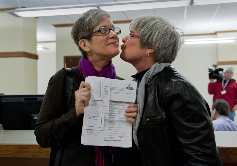 Laurie Johnson and Margaret Witt celebrate attaining their marriage license on Thursday, Dec. 6, 2012, at the Spokane County Courthouse in Spokane, Wash. Washington state now joins several other states that allow gay and lesbian couples to wed. Gov. Chris Gregoire signed a voter-approved law legalizing gay marriage. Because the state has a three-day waiting period, the earliest that weddings can take place is Sunday. (AP Photo/The Spokesman-Review, Dan Pelle) COEUR D\'ALENE PRESS OUT