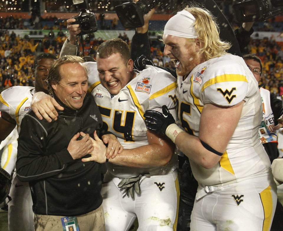West Virginia Mountaineers linebacker Hunter Bittner (54) and offensive linesman Pat Eger (76) hug head coach Dana Holgorsen, left, after defeating Clemson 70-33 at the Orange Bowl NCAA college football game Thursday, Jan. 5, 2012, in Miami . (AP Photo/Lynne Sladky) <strong>Lynne Sladky</strong>