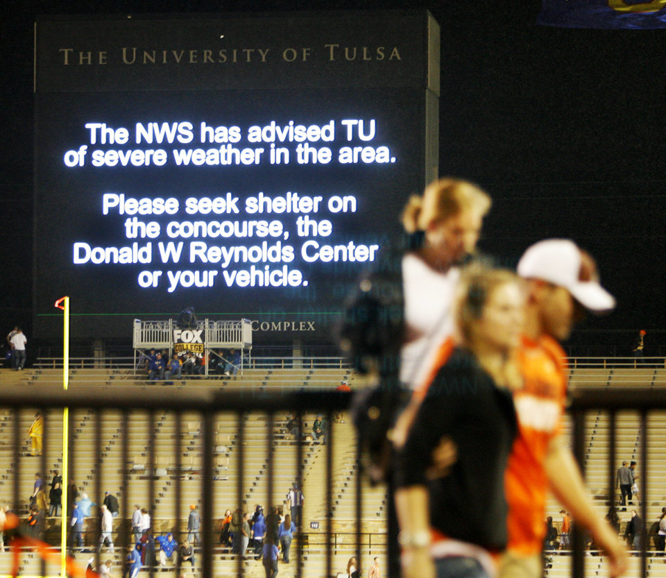 Fans seek shelter as a screen in the stadium warns of severe weather before the Oklahoma State-Tulsa game on Saturday. Photo by Nate Billings, The Oklahoman