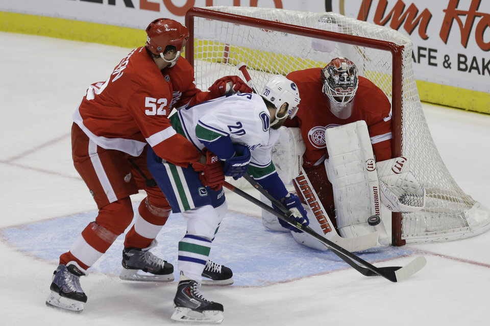 Photo - Vancouver Canucks left wing Chris Higgins (20), defended by Detroit Red Wings defenseman Jonathan Ericsson (52) of Sweden, shoots the puck at goalie Jonas Gustavsson (50) of Sweden during the first period of an NHL hockey game in Detroit, Monday, Feb. 3, 2014. (AP Photo/Carlos Osorio)