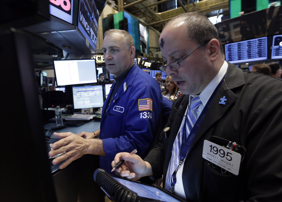 Photo - Trader Jeffrey Vazquez, right, works on the floor of the New York Stock Exchange, Wednesday, March 5, 2014. Stocks are little changed in early trading, a day after setting a record high, as traders were unimpressed by a slight increase in hiring at private companies last month.(AP Photo/Richard Drew)