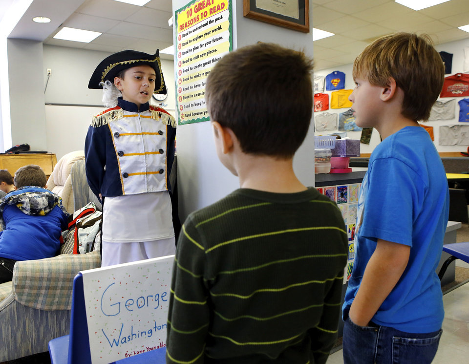 Photo - Two boys pause at Lane Youngblood's station to hear about the heroics of General George Washington. Wearing authentic era attire, students in Rhonda Watkins' fourth and fifth grade social studies classes at Schwartz Elementary School portrayed various figures from the American Revolution period during  a living history museum program in the school's library on Wednesday,  Jan. 30,  2013.  The students selected a historical person from a list provided by Watkins, and  were required to research the subject, write a report and make a verbal presentation about the person. All students in the school were invited to the library to hear the characters tell about their lives.   Photo by Jim Beckel, The Oklahoman