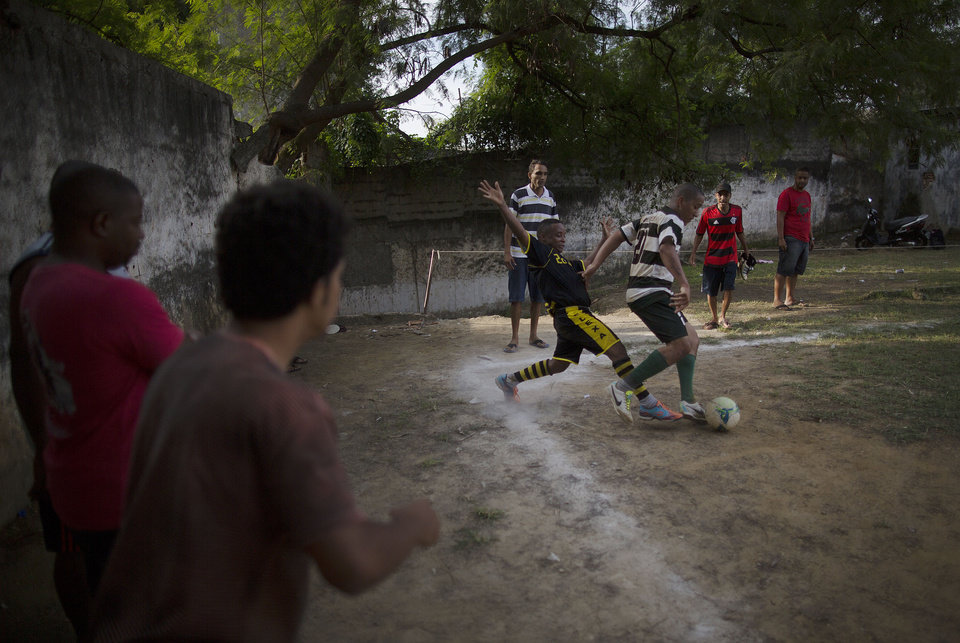 Photo - In this May 3, 2014 photo, players fight for the ball during an amateur soccer match in the Mangueira shantytown of Rio de Janeiro, Brazil. The government says it wants to use the upcoming World Cup to convince international visitors to keep coming back to Brazil after the tournament ends. (AP Photo/Leo Correa)