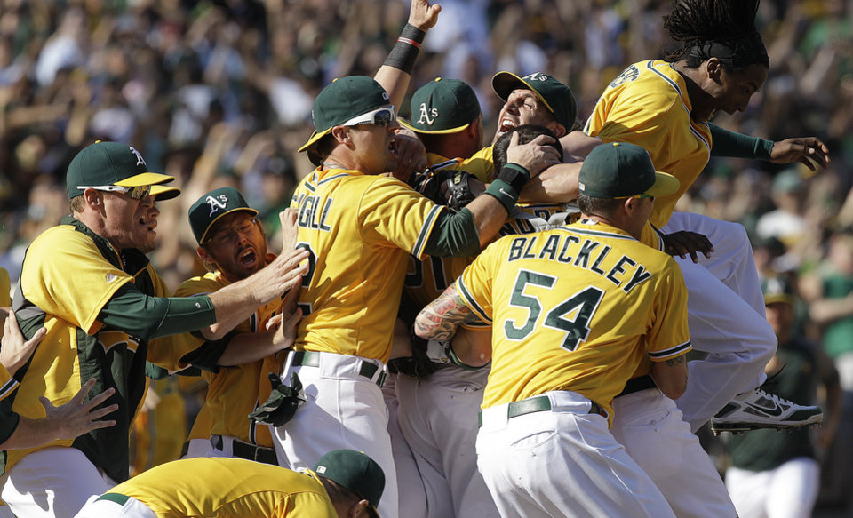 Photo -   Oakland Athletics players celebrate after clinching the American League West at the end of their 12-5 win over the Texas Rangers in a baseball game, Wednesday, Oct. 3, 2012, in Oakland, Calif. (AP Photo/Ben Margot)