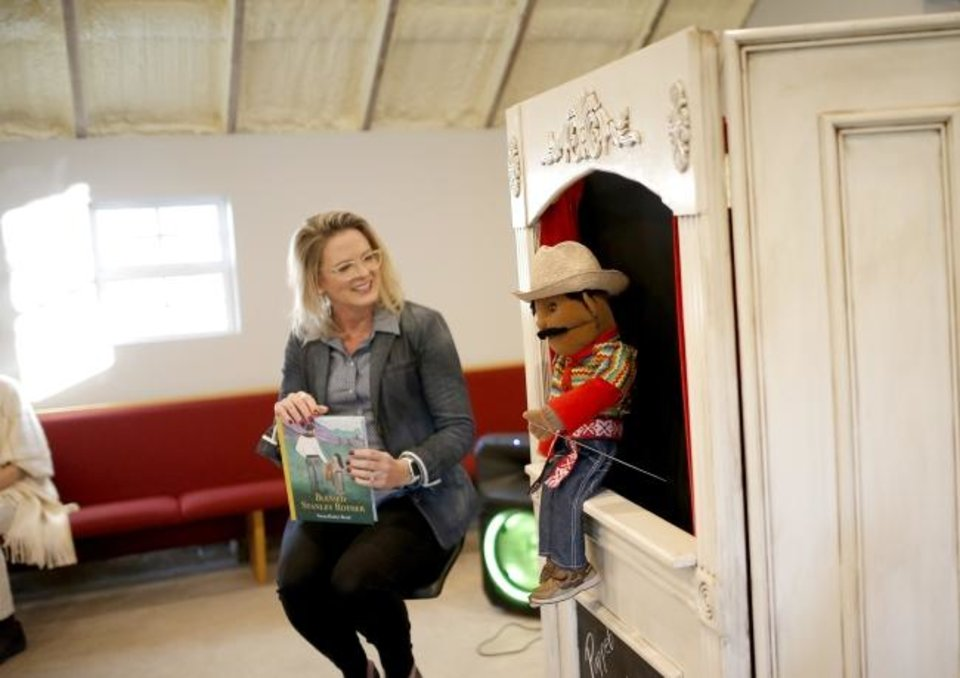 Photo -  Norman author Susan Rother Bond watches as the story of Blessed Stanley Rother is represented in a puppet show. [Sarah Phipps/The Oklahoman]