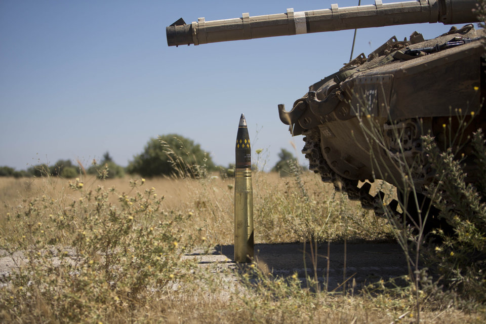 Photo - An ordinance is placed next to a tank following the first death on the Israeli side of the Golan since the Syrian civil war erupted more than three years ago, near the Israeli village of Alonei Habashan, in the area of Tel Hazeka, close to the Quneitra border crossing in the Israeli-controlled Golan Heights, Sunday, June 22, 2014.  A civilian vehicle in the Israeli-controlled Golan Heights was targeted by forces in neighboring Syria on Sunday in an attack that killed a 15-year-old boy and prompted Israeli tanks to retaliate by firing on Syrian government targets, the Israeli military said. (AP Photo/Oded Balilty)