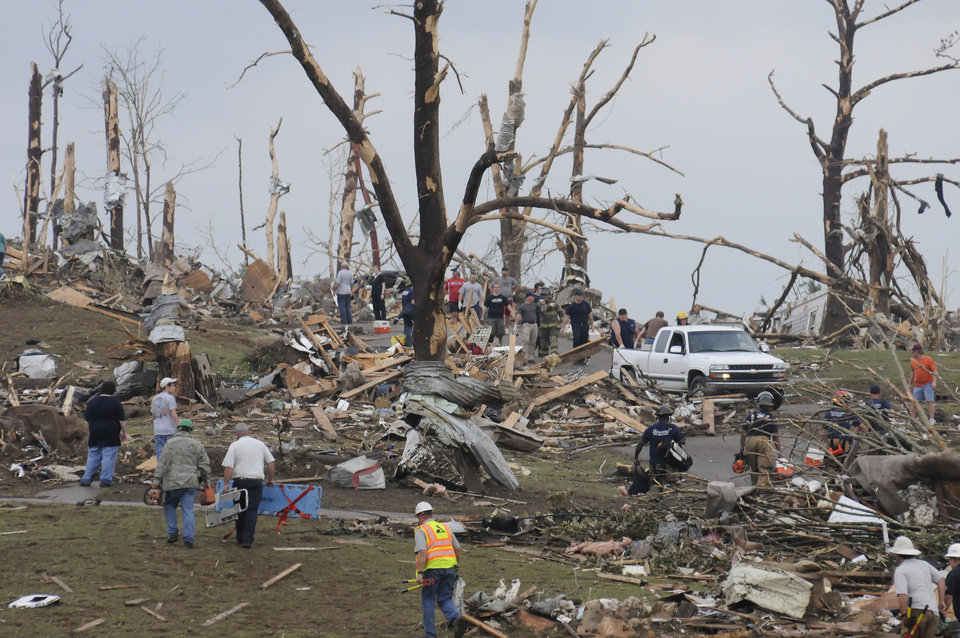 Photo - Rescue workers search a hillside after what appeared to be a tornado ripped through parts of Concord, Ala., Wednesday, April 27, 2011. A wave of tornado-spawning storms strafed the South on Wednesday, splintering buildings across hard-hit Alabama and killing 72 people in four states. At least 58 people died in Alabama alone. (AP Photo/Birmingham News, Jeff Roberts)
