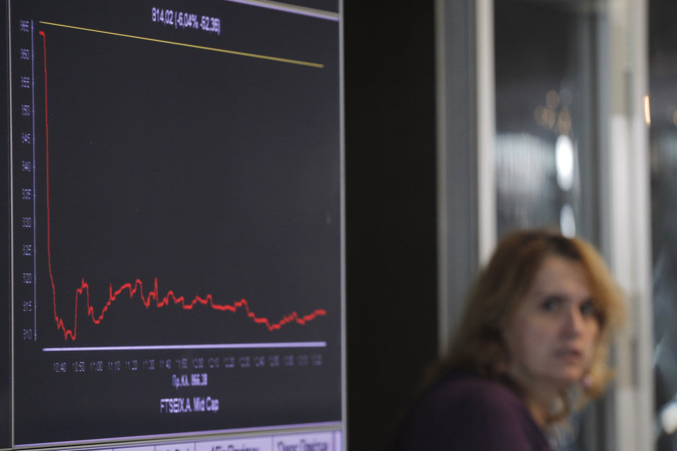 Photo - A woman passes a screen   showing a graph of falling stocks at the Athens Stock Exchange, in Athens, on Tuesday, Nov. 1, 2011. Prime Minister George Papandreou's unexpected decision late Monday led to markets plunging Tuesday on fears that Europe's plan to save the euro will unravel.  (AP Photo/Petros Giannakouris) ORG XMIT: ATH103