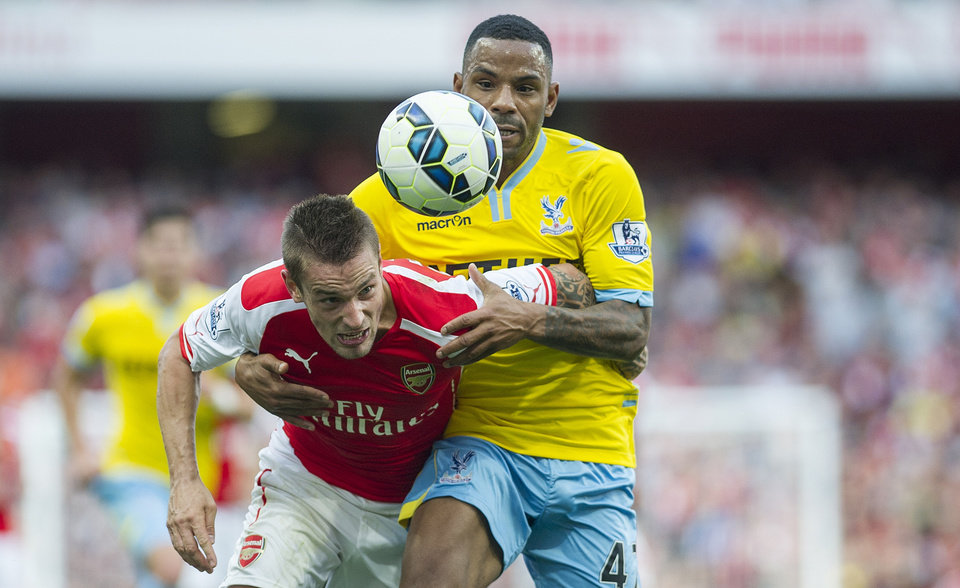 Photo - Arsenal's Mathieu Debuchy, left, fights for the ball with Crystal Palace's Yannick Bolasie, during their English Premier League soccer match, at Emirates Stadium, in London, Saturday, Aug. 16, 2014. (AP Photo/Bogdan Maran)