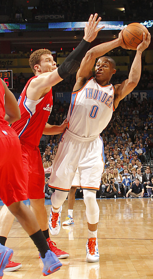 Photo - Oklahoma City Thunder point guard Russell Westbrook (0) looks to pass past Los Angeles Clippers power forward Blake Griffin (32) during the NBA basketball game between the Oklahoma City Thunder and the Los Angeles Clippers at Chesapeake Energy Arena on Wednesday, March 21, 2012 in Oklahoma City, Okla.  Photo by Chris Landsberger, The Oklahoman