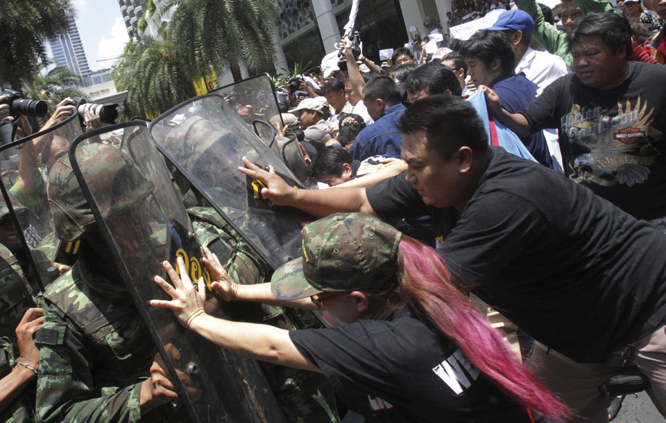 Photo - Protesters push Thai soldiers with riot shields during  an anti-coup demonstration in Bangkok, Thailand, Sunday, May 25, 2014. Gen. Prayuth Chan-ocha in Thailand's ruling junta warned people Sunday not to join anti-coup street protests, saying normal democratic principles cannot be applied at the time, as troops fanned out in central Bangkok to prevent rallies. (AP Photo/Sakchai Lalit)