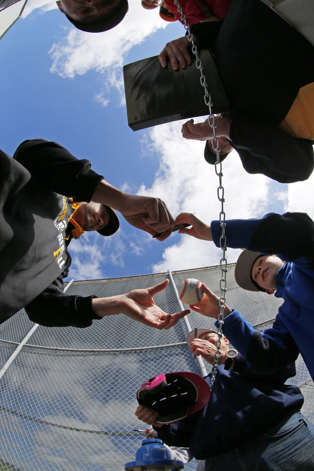 Photo - Pittsburgh Pirates pitcher Jason Grilli, left, signs autographs for fans after the team's first day of baseball spring training for pitchers and catchers, in Bradenton, Fla., Thursday, Feb. 13, 2014. (AP Photo/Gene J. Puskar)