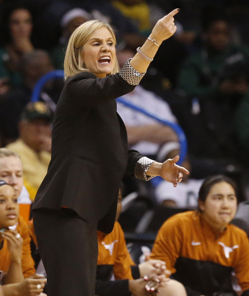 Photo - Texas head coach Karen Aston directs her team in the second half of an NCAA college basketball game against West Virginia in the semifinals of the Big 12 Conference women's tournament in Oklahoma City, Sunday, March 9, 2014. West Virginia won 67-60. (AP Photo/Sue Ogrocki)