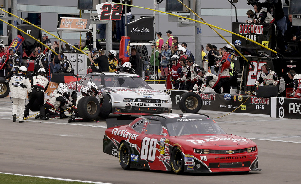 Dale Earnhardt Jr. (88) passes by Brad Keselowski  (22) on pit road during the NASCAR Nationwide Series auto race, Saturday, March 9, 2013, in Las Vegas. (AP Photo/Julie Jacobson)