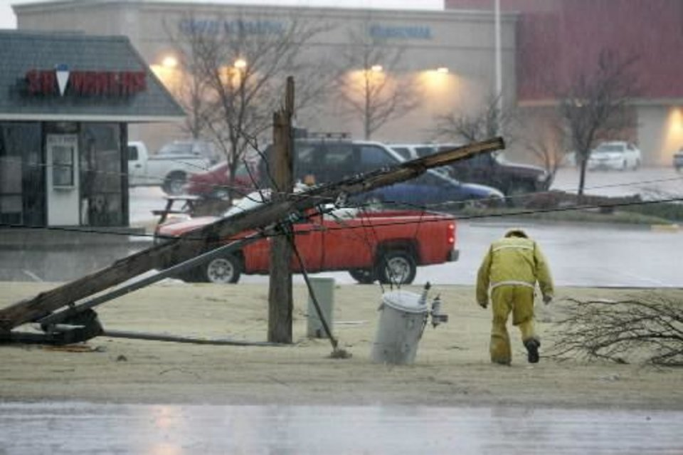 An OG&E worker walks under a downed power line near  Northwest  Expressway and Rockwell in Oklahoma City, Oklahoma February 10, 2009. BY STEVE GOOCH
