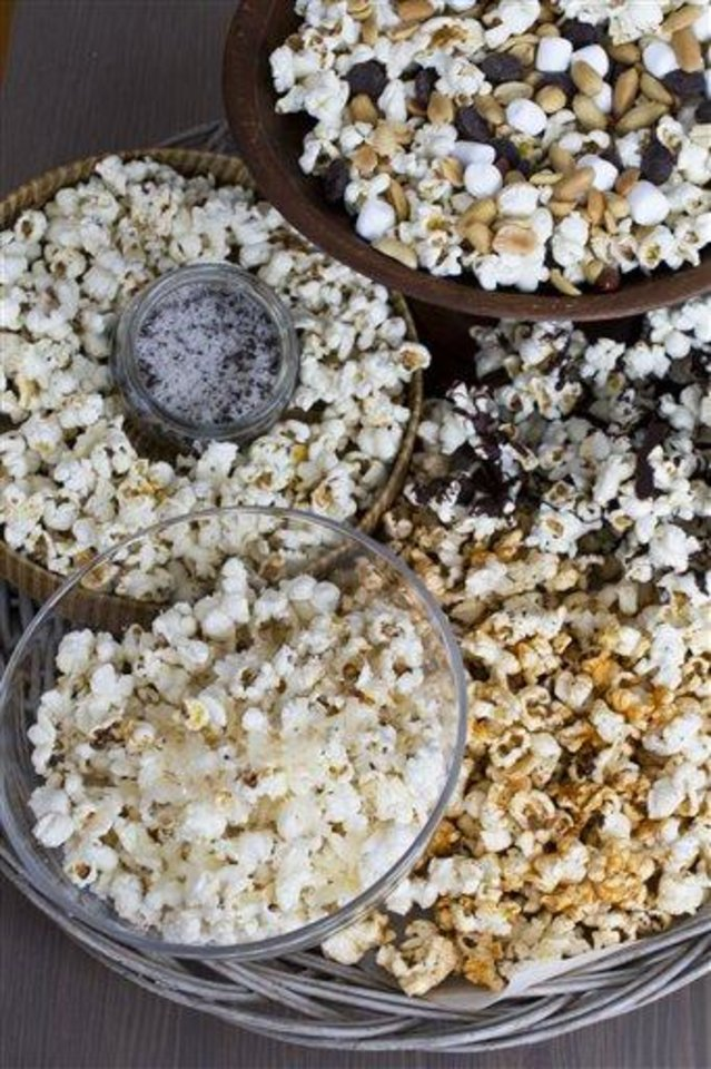 In this image taken on Jan. 28, 2013, the recipe for Stovetop Popcorn Many Ways, from top clockwise, mini marshmallows, chocolate chips and salted peanuts, melted chocolate, sweet and spicy barbeque rub, finely grated parmesan cheese, and truffle salt, is shown in Concord, N.H. (AP Photo/Matthew Mead)