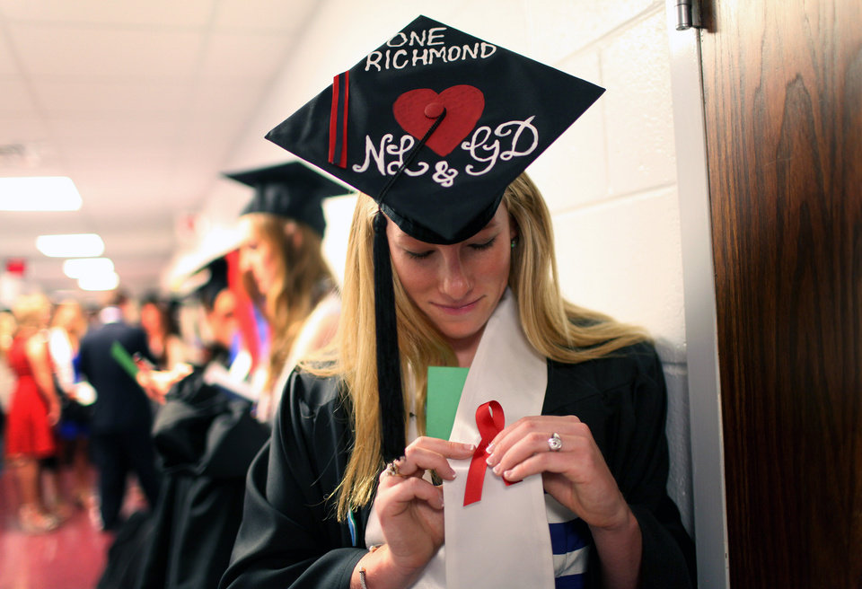 Photo - Laura Jordan wears a red ribbon with her hat decorated with initials of Natalie Lewis and Ginny Doyle before the University of Richmond's Commencement Ceremony in Richmond, Va. on Sunday, May 11, 2014. Lewis, the director of basketball operations of the University of Richmond women's basketball team, and Doyle, the team's associate head coach, died in Friday night's hot air balloon crash in Caroline County. (AP Photo/Richmond Times-Dispatch, Daniel Sangjib Min)