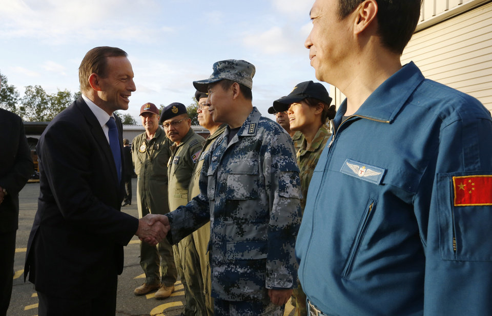 Photo - Australian Prime Minister Tony Abbott, left, greets China's Air Force Senior Colonel Liu Dian Jun, head of China's effort to locate Malaysia Airlines flight MH370, as Chinese Aircraft captain Wang Quan Sheng, right, and others look on during his visit to RAAF Base Pearce near Perth Monday, March 31, 2014. Abbott visited the base on Monday to meet with leaders of international forces being used to locate Malaysia Airlines flight MH370 in the Indian Ocean. (AP Photo/Jason Reed, Pool)