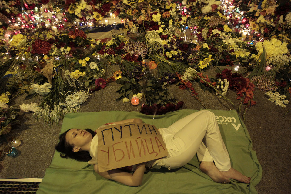 "Photo - Ukrainian woman lies down in front of Dutch embassy holding a poster reading ""Putin is a killer"", in Kiev,Ukraine, Thursday, July 17, 2014.   A Malaysian Airlines passenger jet was shot down in eastern Ukraine on Thursday, and both the Ukrainian government and pro-Russian rebels blamed one another for the attack.(AP Photo/Sergei Chuzavkov)"
