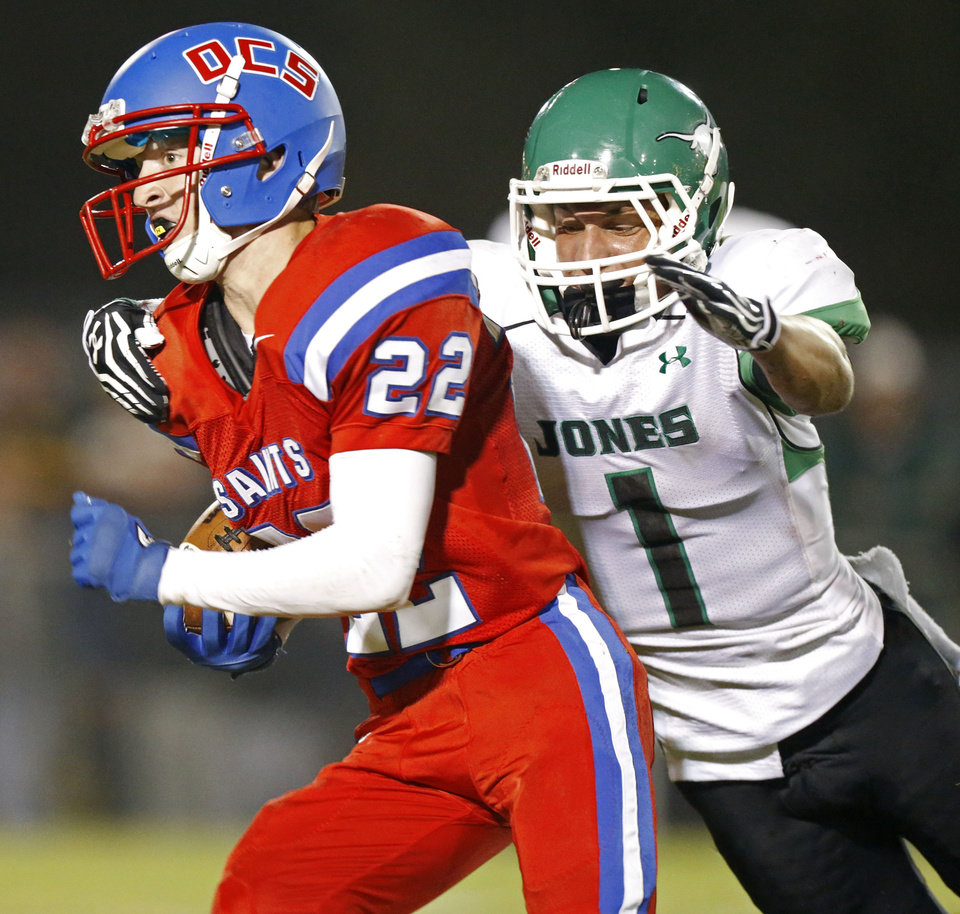 Photo - Conner Sikes of Oklahoma Christian School (OCS) runs past Randal Case of Jones during a high school football game in Edmond, Friday, September 14, 2012. Photo by Bryan Terry, The Oklahoman