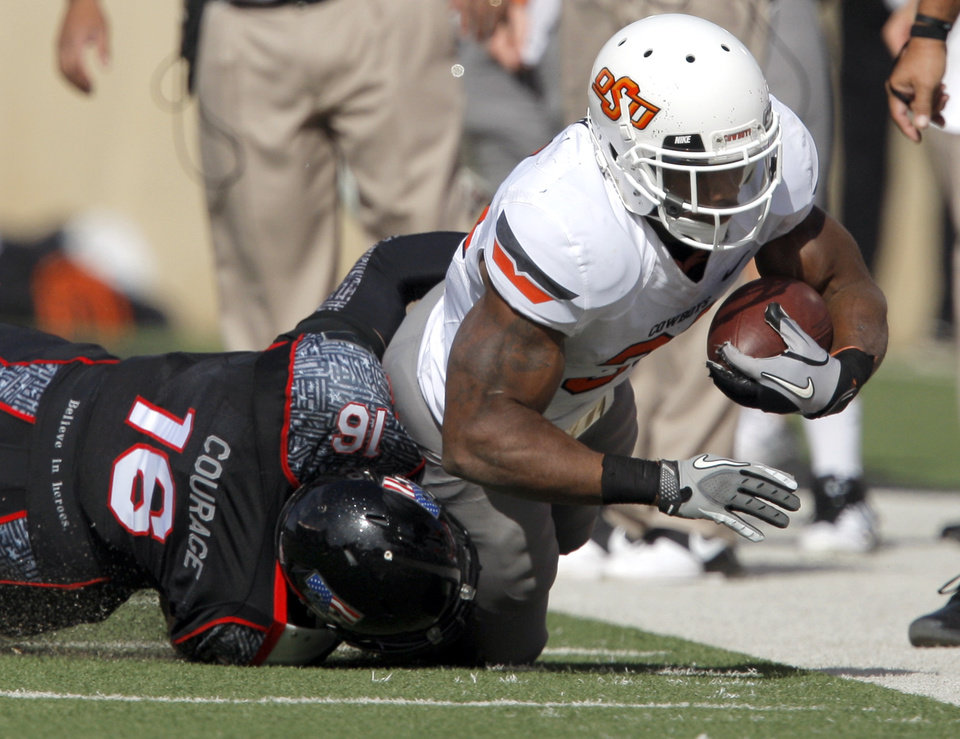Photo - Oklahoma State's Jeremy Smith (31) is tackled by Texas Tech's Cody Davis (16)during a college football game between Texas Tech University (TTU) and Oklahoma State University (OSU) at Jones AT&T Stadium in Lubbock, Texas, Saturday, Nov. 12, 2011.  Photo by Sarah Phipps, The Oklahoman  ORG XMIT: KOD