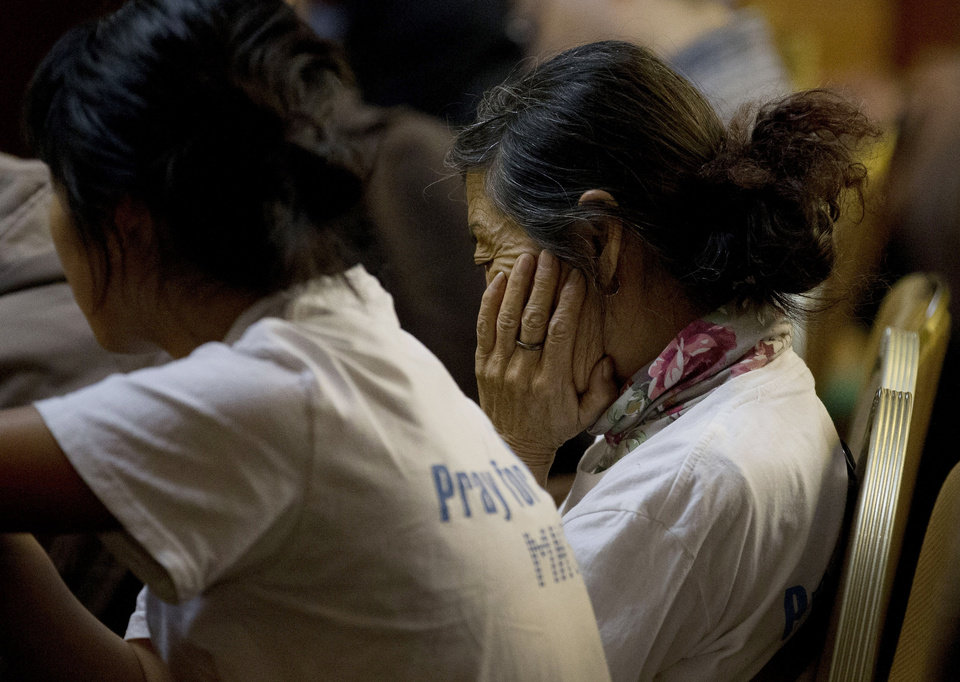Photo - A woman, one of the relatives of Chinese passengers aboard the missing Malaysia Airlines flight MH370, reacts as she and others attend a daily briefing with Malaysian officials at a hotel in Beijing, China Tuesday, April 1, 2014. Although it has been slow, difficult and frustrating so far, the search for the missing Malaysia Airlines jet is nowhere near the point of being scaled back, Australia's Prime Minister Tony Abbott said. The three-week hunt for Flight 370 has turned up no sign of the Boeing 777, which vanished March 8 with 239 people bound for Beijing from Kuala Lumpur. (AP Photo/Andy Wong)