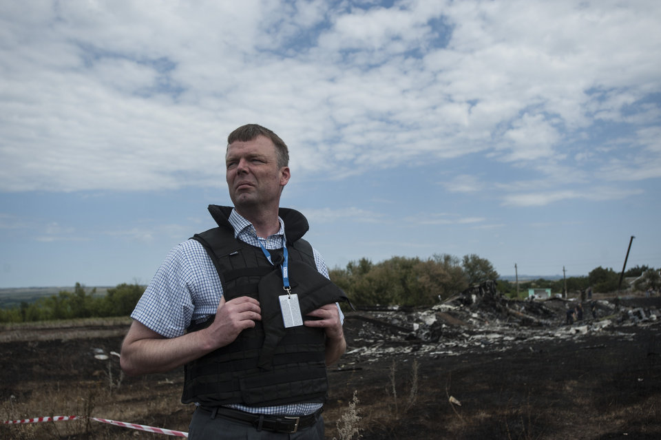Photo - Deputy head of the OSCE mission to Ukraine Alexander Hug looks at the crash site of Malaysia Airlines Flight 17, near the village of Hrabove, eastern Ukraine, Sunday, July 20, 2014. Rebels in eastern Ukraine took control Sunday of the bodies recovered from downed Malaysia Airlines Flight 17, and the U.S. and European leaders demanded that Russian President Vladimir Putin make sure rebels give international investigators full access to the crash site.(AP Photo/Evgeniy Maloletka)