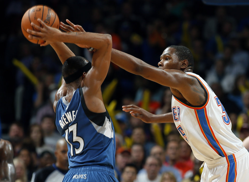 Photo - Oklahoma City's Kevin Durant (35) defends against Minnesota's Corey Brewer (13) during the NBA game between the Oklahoma City Thunder and the Minnesota Timberwolves at the Chesapeake Energy Arena, Sunday, Dec. 1, 2013. Photo by Sarah Phipps, The Oklahoman