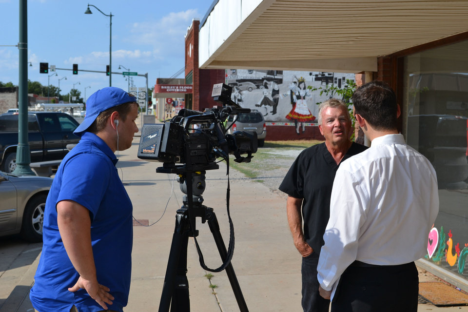 Photo - A TV crew conducts sidewalk interviews a day after a flap at the local school thrust Prague into the national spotlight. Photo by Zeke Campfield, The Oklahoman