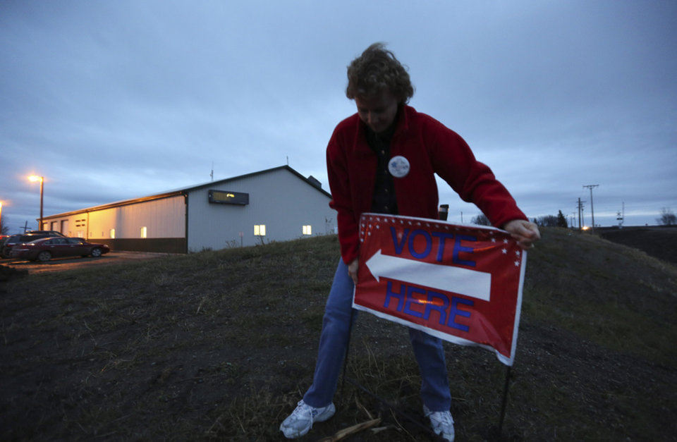 "Election Judge Victoria Collwell places a ""vote here"" sign in the ground in front of the Argusville Firehall Community Center in rural Cass County just before the polls open on Election Day in Argusville, N.D, Tuesday, Nov. 6, 2012. (AP Photo/LM Otero)"