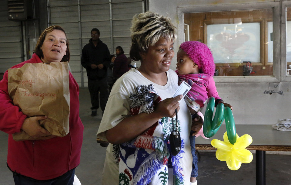 Photo - A woman carries a child as a volunteer follows her carrying her groceries and turkey. Jesus House distributed turkeys and grocery items Tuesday morning,  Nov. 19, 2012. Officials said they had 400 turkeys and food baskets to distribute and people were standing in line when their doors opened at 8 a.m. In less than two yours, all turkeys had been claimed. They will pass out 400 more turkeys and food baskets on Wednesday.  Photo by Jim Beckel, The Oklahoman