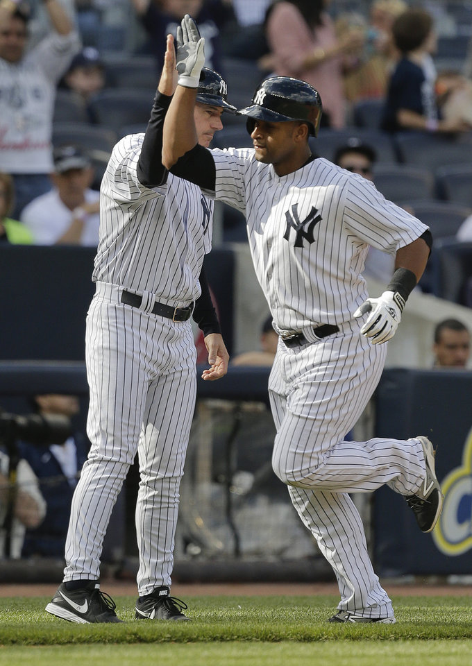 Photo - New York Yankees' Zoilo Almonte (24) is congratulated by third base coach Rob Thompson after hitting a solo home run during the third inning of a baseball game against the Pittsburgh Pirates, Saturday, May 17, 2014, in New York. (AP Photo/Julie Jacobson)