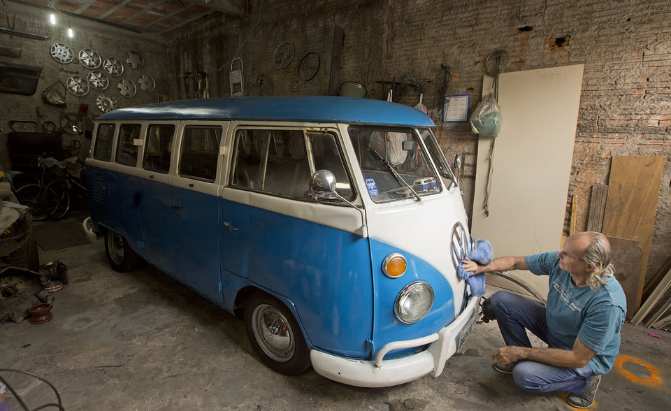 Photo - In this Sept. 16, 2013 photo, Enio Guarnieri wipes the VW emblem of his 1972 Volkswagen van, in Sao Paulo, Brazil. Guarnieri, who keeps his blue and white van or Kombi in his cluttered garage, bought the vehicle a year ago to stoke childhood memories. When he was 10, his father taught him to drive a Kombi.