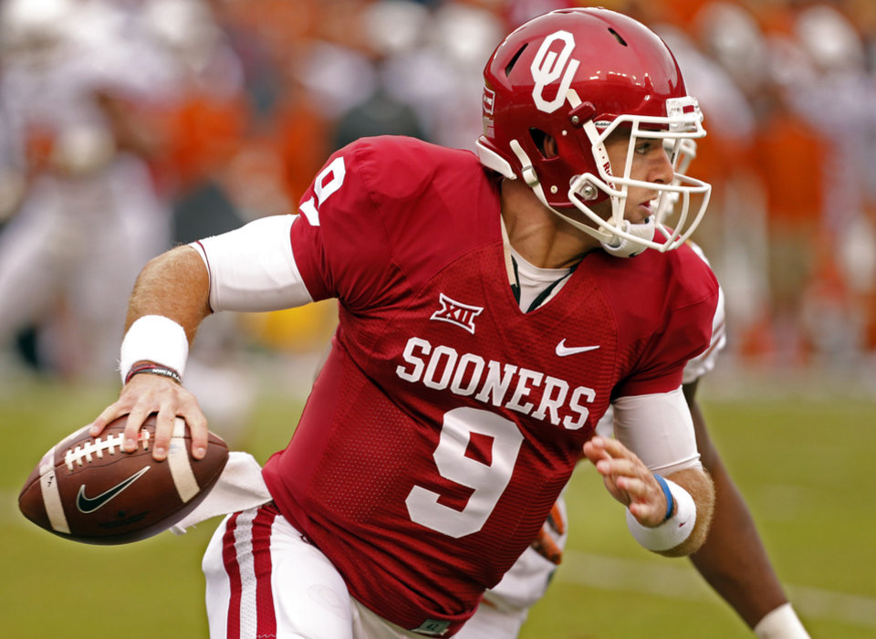Photo - Oklahoma's Trevor Knight (9) looks for a receiver during the Red River Showdown college football game between the University of Oklahoma Sooners (OU) and the University of Texas Longhorns (UT) at the Cotton Bowl in Dallas, Texas on Saturday, Oct. 11, 2014. 