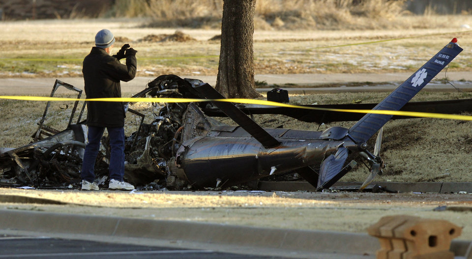 Investigators with the FAA look over the wreckage of a medical helicopter which crashed Friday, Feb. 22, 2013 in front of the Saint Ann Retirement Center in Oklahoma City, Okla. Two people were killed in the crash and a third person was injured.  (AP Photo/The Oklahoman,Paul Hellstern) LOCAL TV OUT (KFOR, KOCO, KWTV, KOKH, KAUT OUT); LOCAL INTERNET OUT; LOCAL PRINT OUT (EDMOND SUN OUT, OKLAHOMA GAZETTE OUT) TABLOIDS OUT