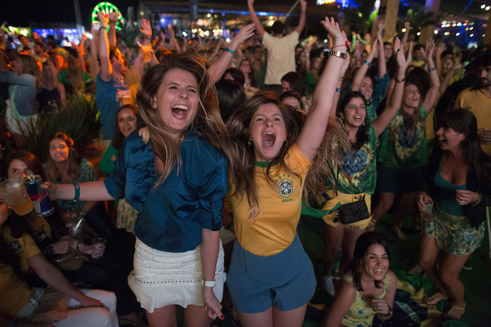 Photo - Soccer fans celebrate the second goal scored by Brazil striker Neymar, during a live broadcast at a World Cup viewing party at the Jockey Club, in Rio de Janeiro, Brazil, Thursday, June 12, 2014. After taking the early lead in the opening match of the international soccer tournament, Croatia fell 3-1 to the five-time champion Brazil. (AP Photo/Leo Correa)